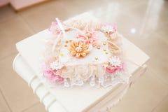 Anneaux de mariage d'or sur l'oreiller blanc décoré des fleurs Photo stock