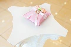 Anneaux de mariage d'or sur l'oreiller blanc décoré des fleurs Image stock