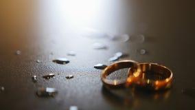 Anneaux de mariage d'or sur la table avec des gouttes de l'eau, foyer de support banque de vidéos