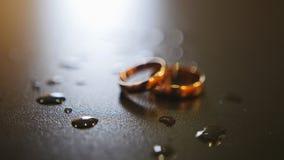 Anneaux de mariage d'or sur la table avec des gouttes de l'eau, tir de glisseur banque de vidéos