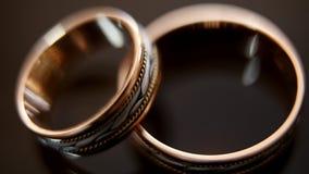Anneaux de mariage d'or sur la table en verre de miroir - on se trouve dessus des autres, macro banque de vidéos
