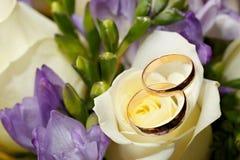 Anneaux de mariage d'or sur le bouquet des fleurs pour la jeune mariée Images stock
