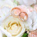Anneaux de mariage d'or sur le bouquet des fleurs pour la jeune mariée image libre de droits
