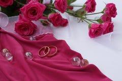 Anneaux de mariage d'or sur le tissu rose avec le ruban et les roses blancs Photo libre de droits