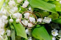 Anneaux de mariage d'or sur les lis de la vallée Images stock