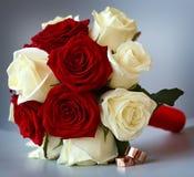 Anneaux de mariage d'or sur un bouquet des fleurs pour la jeune mariée Images stock