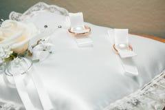 Anneaux de mariage d'or sur un coussin blanc photo libre de droits