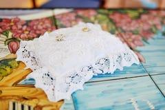 Anneaux de mariage d'or sur un oreiller blanc Image libre de droits