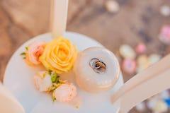 Anneaux de mariage d'un couple nouveau-marié sur un coussin pour des anneaux Photographie stock libre de droits