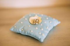Anneaux de mariage d'un couple nouveau-marié sur un coussin pour des anneaux Image stock