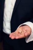 Anneaux de mariage dans des mains au marié Image libre de droits
