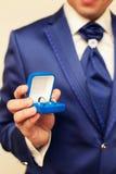 Anneaux de mariage dans des mains au marié Photo stock