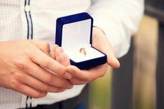 Anneaux de mariage dans des mains au marié Images libres de droits
