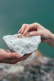 Anneaux de mariage dans des mains de jeune mariée sur le fond en pierre Image stock