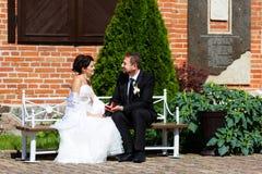 Anneaux de mariage dans des mains de marié et de jeune mariée Image stock