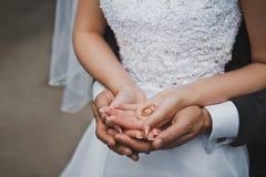 Anneaux de mariage dans des mains des couples nouveau-mariés 2070 Photographie stock libre de droits