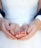 Anneaux de mariage dans des mains des couples nouveau-mariés Images stock
