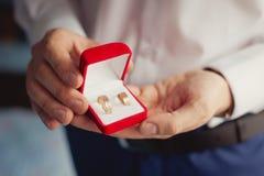 Anneaux de mariage dans des mains du ` s de marié Photographie stock