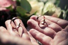 Anneaux de mariage dans des mains du ` un s d'homme Photo libre de droits