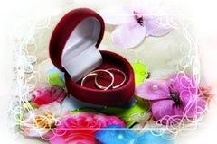 Anneaux de mariage dans la boîte rouge sur la carte d'invitation Image libre de droits