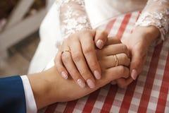 Anneaux de mariage dans les mains des hommes et des femmes Photo stock