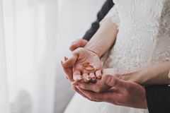 Anneaux de mariage dans les mains des nouveaux mariés 1214 Image libre de droits