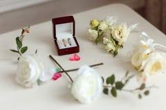 Anneaux de mariage dans une belle boîte en bois Arrangement floral avec les roses blanches Photographie stock