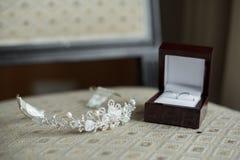 Anneaux de mariage dans une boîte brune et une couronne Photos stock