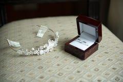 Anneaux de mariage dans une boîte brune et une couronne Images stock