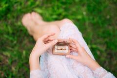 Anneaux de mariage dans une boîte en bois pour des anneaux dans les mains du brid Images stock