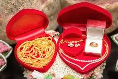 Anneaux de mariage dans une boîte sur un fond de fleur Images stock