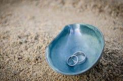 Anneaux de mariage dans une coquille sur la côte Images libres de droits