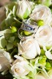 Anneaux de mariage en fleurs Photographie stock