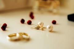 Anneaux de mariage et boucles d'oreille sur la table Image libre de droits