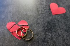 Anneaux de mariage et coeur rouge brisé Fond noir Le conce Image libre de droits