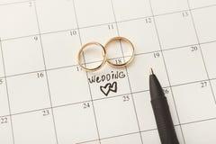 Anneaux de mariage et d'or de Word sur le calendrier Photographie stock libre de droits