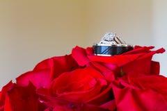 Anneaux de mariage et fleurs rouges Images stock