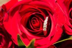 Anneaux de mariage et fleurs rouges Photos libres de droits