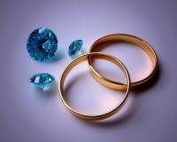 Anneaux de mariage et gemmes bleues Photographie stock libre de droits