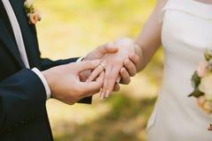 Anneaux de mariage et mains des jeunes mariés Images libres de droits