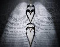 Anneaux de mariage et ombre en forme de coeur au-dessus de bible Photos stock