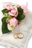 Anneaux de mariage et roses roses Image libre de droits