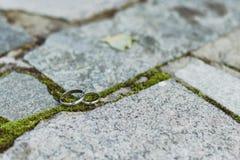 Anneaux de mariage de l'or blanc sur le fond en pierre Images libres de droits