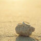Anneaux de mariage mis sur la plage Photographie stock libre de droits