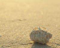 Anneaux de mariage mis sur la plage Images stock