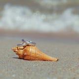 Anneaux de mariage mis sur la plage Images libres de droits