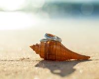 Anneaux de mariage mis sur la plage Photographie stock