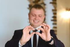Anneaux de mariage de participation de marié sur la paume dans le costume, la main du marié, anneau de mariage dans la main de ma image libre de droits