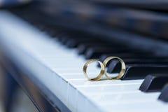 Anneaux de mariage de piano et de fond noir et blanc images stock