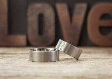 Anneaux de mariage de platine devant l'amour de mot Photo libre de droits